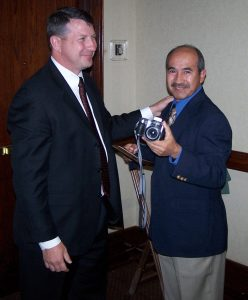 Thomas Escobar (right) accepts congratulations after having received a 2006 TMS Service Award for his exceptional contributions as Editor of TMS News.