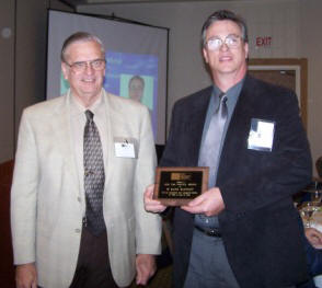Mark McGinley (right) accepts congratulations from John Chrysler (left) upon receiving a 2008 TMS Service Award.