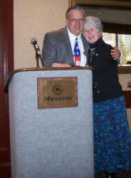 Linda Miller (right) hugs John Chrysler (left) after receiving a 2007 TMS Service Award for her exceptional contributions at TMS meetings.