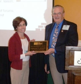 TMS President John Chrysler congratulates Tina Subasic on receiving the 2011 President's Award during the Annual Meeting Awards Luncheon.