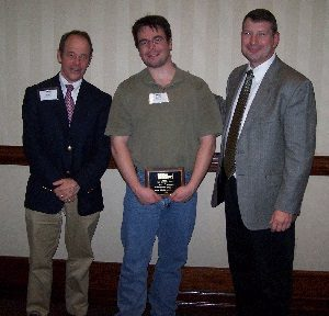 Jason Thompson (center) accepts congratulations upon receiving a 2006 TMS Service Award for his exceptional service as Secretary of the Masonry Standards Joint Committee (MSJC).
